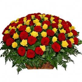 Желтые и красные розы с зеленью в корзине